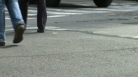 Pedestrians and traffic (2 of 16). Pedestrians and vehicles cross a city intersection stock video footage