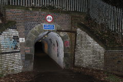 Pedestrians only. Tunnel in Riversley Park Nuneaton Warwickshire at night Cyclists must dismount white brick work Royalty Free Stock Photos