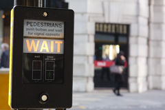 Pedestrians wait. A British pedestrian crossing button with illuminated wait sign Royalty Free Stock Images