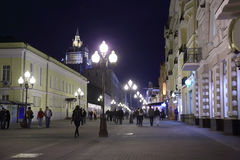 Pedestrians walk on Arbat street. Lighted by lanterns in Moscow, Russia Royalty Free Stock Photography
