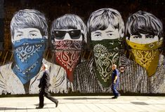 Pedestrians walk past large Beatles graffiti mural. Pedestrians walk past a large Beatles graffiti mural in a quiet street in the city of London, England stock photography