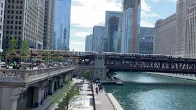 Pedestrians walk on Upper Wacker and lower city on riverwalk alongside the Chicago River as el trains pass over Wells Street. Bridge during morning commute stock video