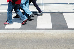Pedestrians walking. Detail of three persons legs crossing the street Stock Photo