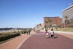 Pedestrians Walking Along Paved Promenade on Beach Front Stock Photo
