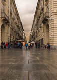 Pedestrians walking along a wet street in Turin. Architecture in one of the squares in Turin, Italy Royalty Free Stock Photos