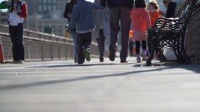 Pedestrians walking on a bridge. Pedestrians walk on a busy bridge walkway on a sunny, autumn day stock video