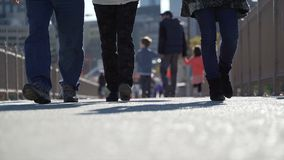Pedestrians walking on a bridge. Pedestrians walk on a busy bridge walkway on a sunny, autumn day stock video footage