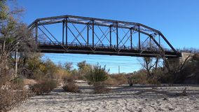Pedestrians Walking on Former Train Bridge. Pedestrians on a park trail walk across a former train bridge that spans a dry creek bed stock video
