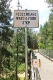Pedestrians Watch Your Step sign on a narrow footbridge Stock Photos