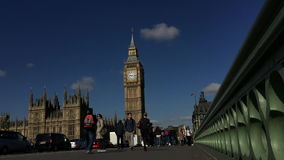 Pedestrians on Westminster Bridge with Big Ben London. LONDON, UK - APRIL 27, 2015: Pedestrians travel along Westminster Bridge against a bright morning view of stock video footage