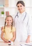 Pediartician. Picture of little smiling girl visiting her doctor at clinic Royalty Free Stock Photos