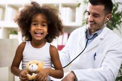 Pediater arts die jong geitje onderzoeken Stock Afbeeldingen