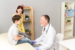 Pediater arts die kind onderzoeken stock foto's
