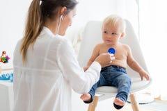 Pediater die babyjongen onderzoeken Arts die stethoscoop met behulp van aan lis royalty-vrije stock foto's