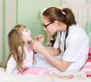 Pediater die de keel van het meisje onderzoeken stock afbeeldingen