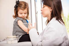 Pediater die een meisje een schot geven Stock Fotografie