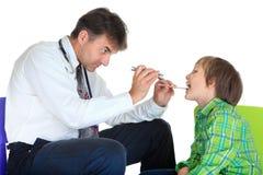 Pediater die jongen onderzoekt stock afbeelding
