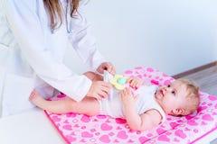 Pediater die zuigeling onderzoeken stock afbeeldingen
