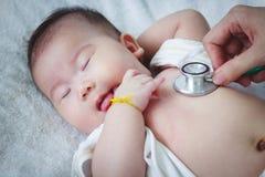 Pediater die zuigeling onderzoeken Twee maanden baby het Aziatische meisje liggen royalty-vrije stock fotografie