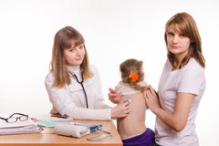 Pediater het luisteren de rug van de stethoscoopbaby, die mum houdt Stock Foto