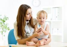 Pediatervrouw het onderzoeken van jong geitje met Royalty-vrije Stock Fotografie