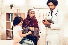 Pediatra árabe Appointment Mom com filho doente Doutor masculino muçulmano seguro Conceito do hospital Conceito saudável pediatri fotos de stock