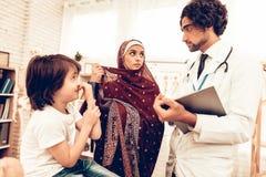Pediatra arabo Appointment Mom con il figlio malato immagine stock