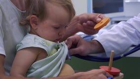 Pediatra che ascolta la respirazione della bambina con lo stetoscopio stock footage