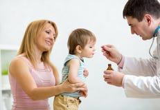 Pediatra che dà la dose del cucchiaio di medicina Fotografia Stock
