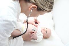 Pediatra con el bebé que comprueba defecto posible del corazón Foto de archivo