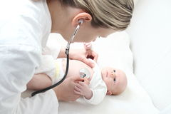 Pediatra con il bambino che controlla difetto possibile del cuore fotografia stock