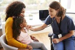 Pediatra de sexo femenino Wearing Scrubs Listening al pecho de las muchachas con el estetoscopio en oficina del hospital fotos de archivo libres de regalías