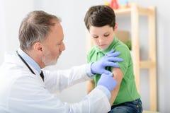 Pediatra del doctor que inyecta la vacuna foto de archivo libre de regalías