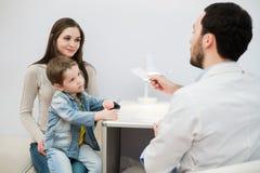Pediatra doktorski egzamininuje dziecko Macierzysty mienia dziecko w ona ręki zdjęcie stock