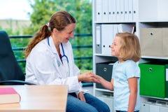 Pediatra en la capa blanca del laboratorio que saluda al pequeño paciente Imagenes de archivo
