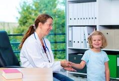 Pediatra en la capa blanca del laboratorio que saluda al pequeño paciente Fotografía de archivo libre de regalías