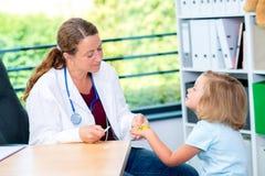 Pediatra en la capa blanca del laboratorio y el pequeño paciente Fotos de archivo libres de regalías