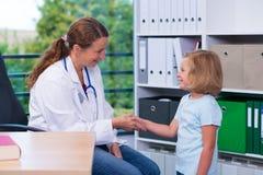 Pediatra en la capa blanca del laboratorio y el pequeño paciente Foto de archivo libre de regalías