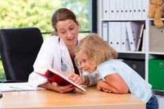 Pediatra en la capa blanca del laboratorio y el pequeño paciente Fotografía de archivo