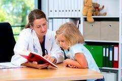 Pediatra en la capa blanca del laboratorio y el pequeño paciente Fotografía de archivo libre de regalías