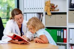 Pediatra en la capa blanca del laboratorio y el pequeño paciente Imagenes de archivo