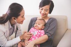 Pediatra fêmea asiático que examina um bebê no la da mãe Fotos de Stock Royalty Free