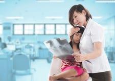 Pediatra fêmea novo que explica o raio X Imagens de Stock Royalty Free