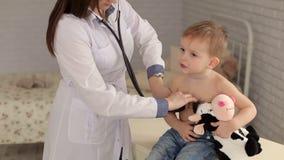 Pediatra femminile che esamina ragazzino sveglio con lo stetoscopio archivi video