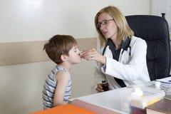 Pediatra Giving Cough Syrup al muchacho enfermo en el cuarto de consulta foto de archivo libre de regalías