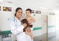 Pediatra latino en el hospital con un bebé Fotos de archivo