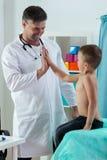 Pediatra que dá a menino uns cinco Fotografia de Stock