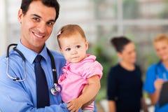 Pediatra que detiene al bebé Imágenes de archivo libres de regalías
