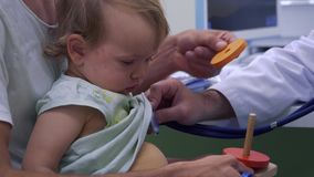 Pediatra que escucha la respiración de la niña con el estetoscopio metrajes