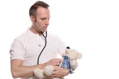 Pediatra que escuta um coração dos ursos de peluche Fotografia de Stock Royalty Free